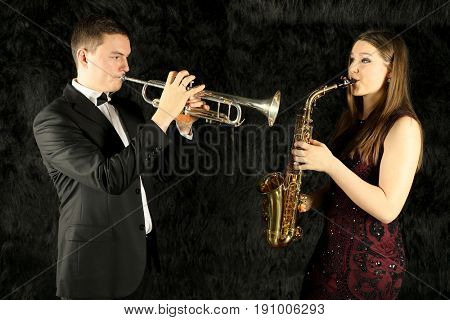 Two musicians playing on wind instruments on a black fur ground
