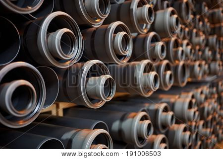Gray plastic pipes at indoor storage, shallow dof.