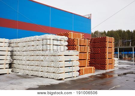 Plenty of red and white plastic water pipes at outdoor storage.