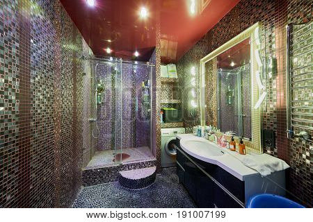 Bathroom with shower cabin, basin, frontload washer. Walls and floor covered with ceramic tiles.