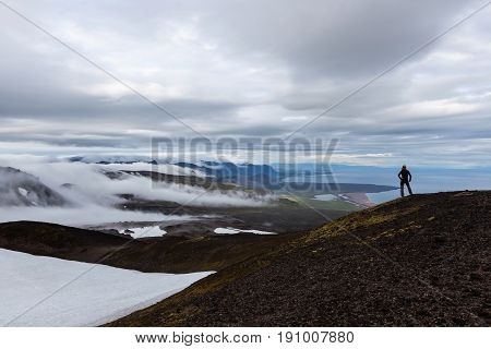 Solitude Landscape In Iceland Mountains. Single Traveler Standing On The Hill And Looking To The Dis