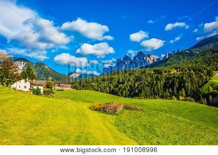 The valley is surrounded by a dentate wall of rocks. Charming chalet on a green grassy slope. Warm autumn in the Dolomites. The concept of ecological tourism