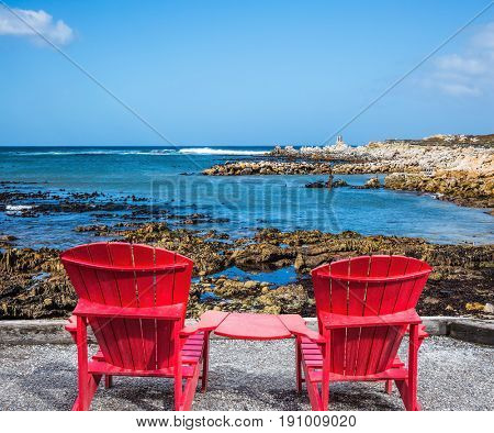 Two red armchairs chaise longue by Atlantic ocean. Boulders Penguin Colony in the Table Mountain National Park, South Africa. The concept of ecotourism