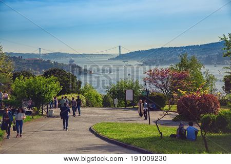 ISTANBUL, TURKEY - APRIL 29, 2017: People walking at Otagtepe park with beautiful view of the Bosphorus, the Bosphorus Bridge which connects Asian and European sides of Istanbul, Beykoz