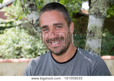a smiling man thirties outdoor happy unshaven