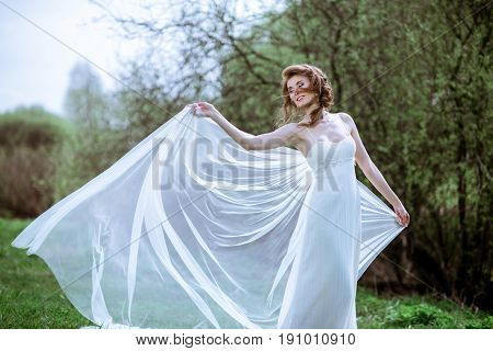 Blonde bride in fashion white wedding dress with makeup. Wedding day of bride in bridal gown. Beauty woman in veil. Fashion blonde model outdoors. Beauty portrait of model in white bridal dress
