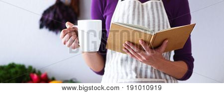 A young woman standing in her kitchen drinking tea and holding a cookbook