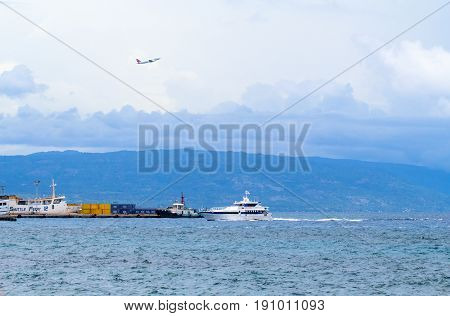Dumaguete Philippines - 13 May 2017: city port with island silhouette. Urban seaside and sea transport. Port shipping containers. Passenger flight over sea. Airplane and ship. Tropical island hopping