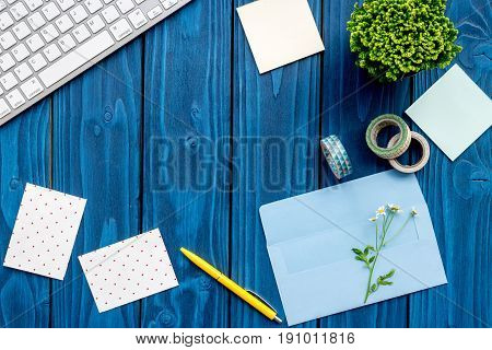 colorful home office desk with plants, notes and keyboard on blue wooden background top view mock up