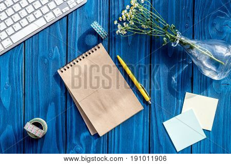 colorful work space with keyboard, notebook and flowers for home office blue wooden desk background top view mockup