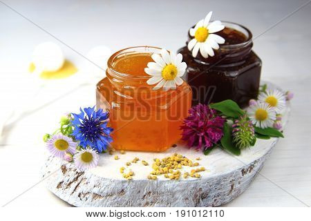 honey in glass jars with wildflowers on the Board