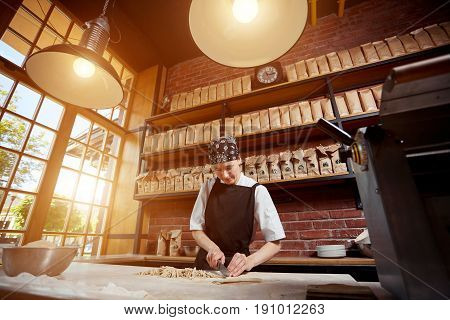 Woman cutting knead in restaurant. Horizontal indoors shot of woman in cafeslicing noodles. Making pasta. Making pasta in restaurant.