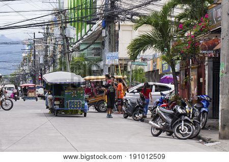 Dumaguete Philippines: 13 May 2017: city street view with local transport and people. Tourist transport. Transport and traffic in Philippines. Asian town street scene. People of Philippines country