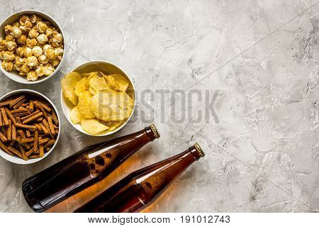 watching TV set with chips, pop corn and crumbs on stone table background top view mock up