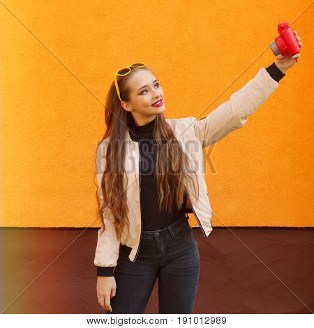 Young pretty hipster girl in yellow sunglasses make selfie by pink instant camera on orange wall.