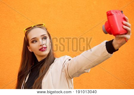 Young pretty hipster girl in yellow sunglasses make selfie by pink instant camera on orange wall. Urban style