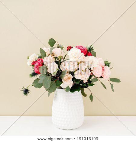 Beautiful flowers bouquet: bombastic roses blue eringium eucalyptus branches in flowerpot at pale pastel beige wall. Floral lifestyle composition.