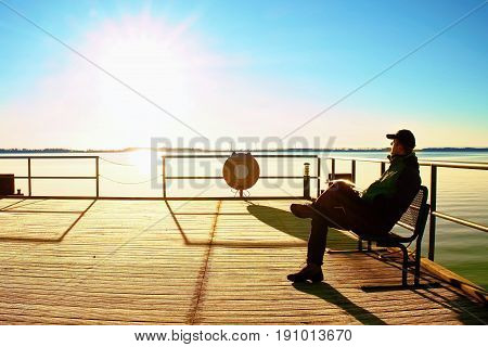 Man Sit On Wharf And Enjoy Morning At Sea. Sunny Clear Blue Sky, Smooth Water Level