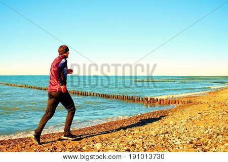 Tall man in dark sportswer running and exercising on stony beach at breakwater. Vivid and vignetting effect