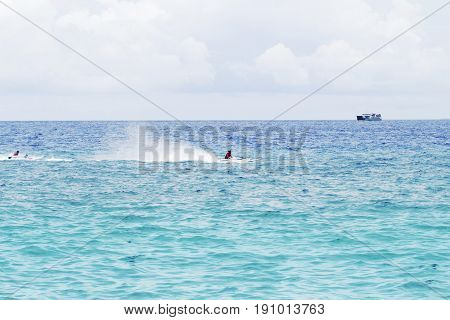 Seawater landscape with cargo ship on horizon and speedboat. Sea view of boats and sailors. Motor boats race in sea. Marine racing championship. High speed motorboat sail. Sea water spray. Water sport