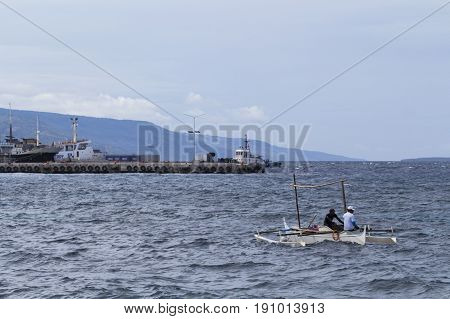 Dumaguete Philippines - 13 May 2017: sea landscape with boats and local sailors. Urban seaside with sea port. Modern and traditional shipping. Fisherman boat. Local lifestyle of developing country