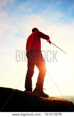 Tourist In Windcheater With Sporty Trecking  Poles In Hands Stand On Rocky View Point. Spring Commin