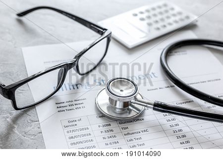 medical treatmant billing statement with stethoscope and glasses on stone desk background