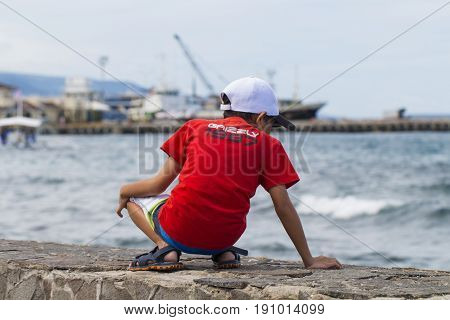 Dumaguete Philippines - 13 May 2017: a boy in red t-shirt looks at the sea and port. Sea travel. Island hopping in Philippines. Little boy and seaside landscape. Urban seascape with lonely child