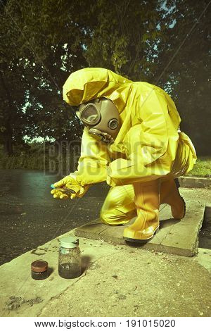 Man in chemical protective suit collecting samples of water contamination