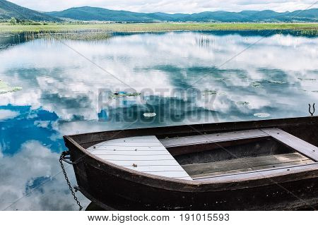 Boat on the shore of the lake. Reflection of the sky in the water. Rest on the lake, peace and quiet.