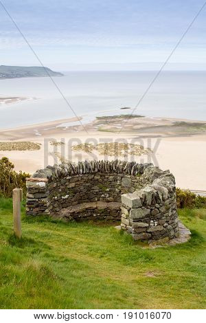 Upright shot of old fort stone look out and Barmouth beach and sea behind a beautiful Welsh coastal landscape