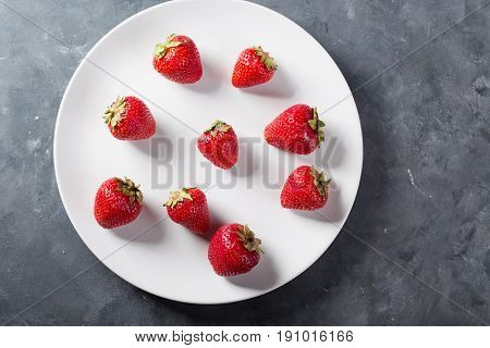 Strawberry on a white plate. Fresh strawberry on a light background . Red strawberry. Loosely laid strawberries in different positions. Copyspace. Valentine's Day background.