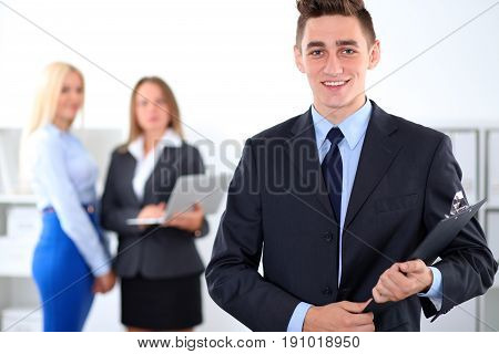 Cheerful business man in office with colleagues in the background, sturt-up team.