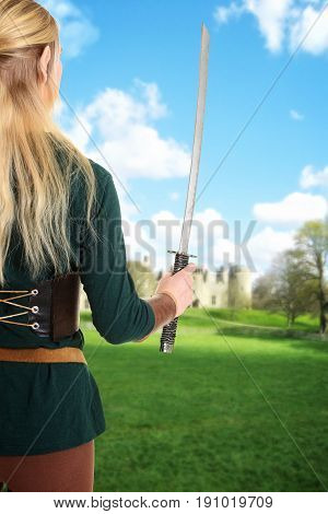 back of female elf holding sword looking at castle