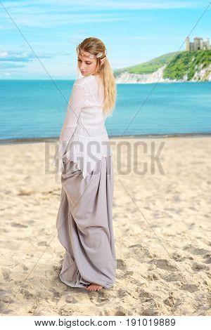female elf on a beach wearing a crown