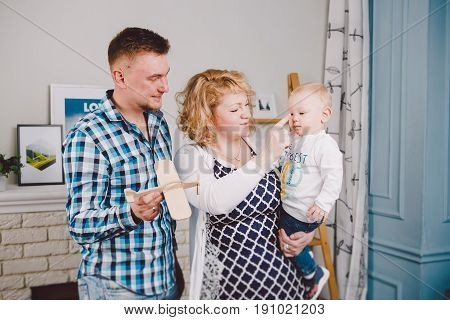 A Family Of Three. Mom, Dad, Son Holds His Mother For One Year, Dad Holds A Toy Wooden Plane.