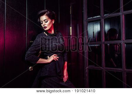Portrait of beautiful fashion model in classic black dress, makeup and hairstyle near dark door standing and posing and red light from window glows on her. studio shot.