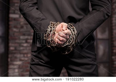 Silent murderer hands in iron chain, back view