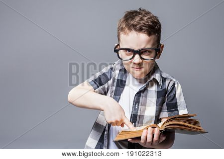 Strict boy in glasses with book in hands,