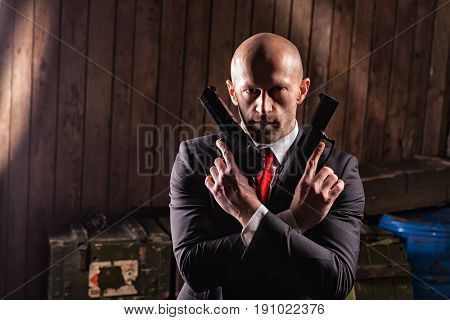 Bald contract killer in suit with two pistols