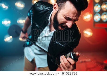 Bearded performer with microphone sing a song