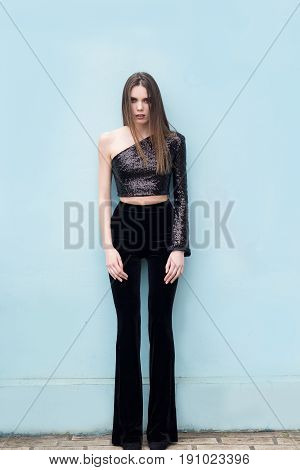 Beautiful brunette woman in stylish pants and tops posing on a blue background. Fashion model. Total black look. Luxury look.