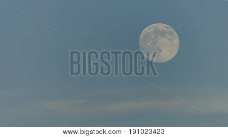 Day moon with light blue sky in spring evening