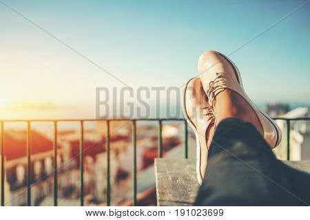 Female feet with glossy pale pink shoes relaxing on wooden table and touristic european city near sea with multiple houses in blurred background with copy space for advertising logo or your texts