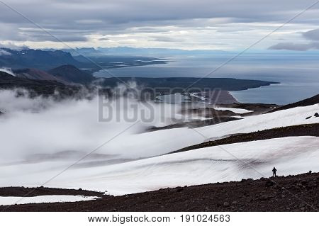 Solitude Landscape In Iceland Mountains. Single Traveler Standing On The Slope Of Volcano Looking To