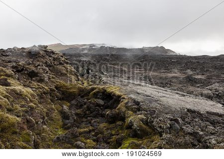 Apocalyptic Smoking Black Landscape Of Krafla Crater With Some Alive Green Moss. Lava Desert - Still