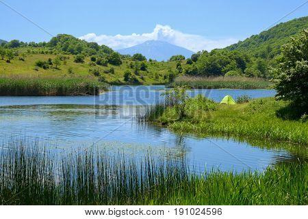 wild camp on Biviere Lake in Nebrodi Park, on background Etna Mount, Sicily