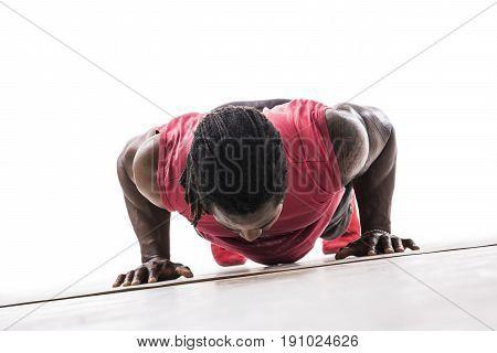 Unrecognizable black young man in studio doing push-ups on the floor. Tilted shot