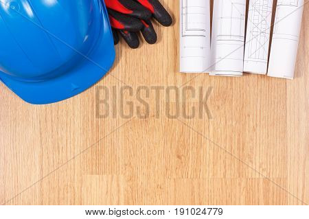 Rolls Of Electrical Drawings, Protective Blue Helmet And Gloves, Accessories For Engineer Jobs
