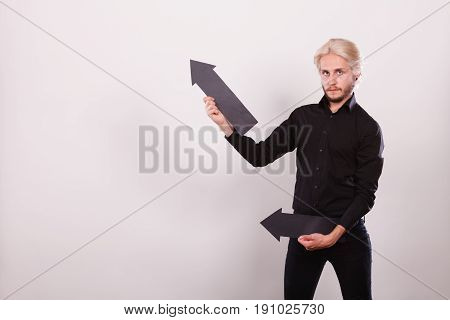 Planning directions choices concept. Man holding two black arrows pointing in the same directions. Indoor shot on light background